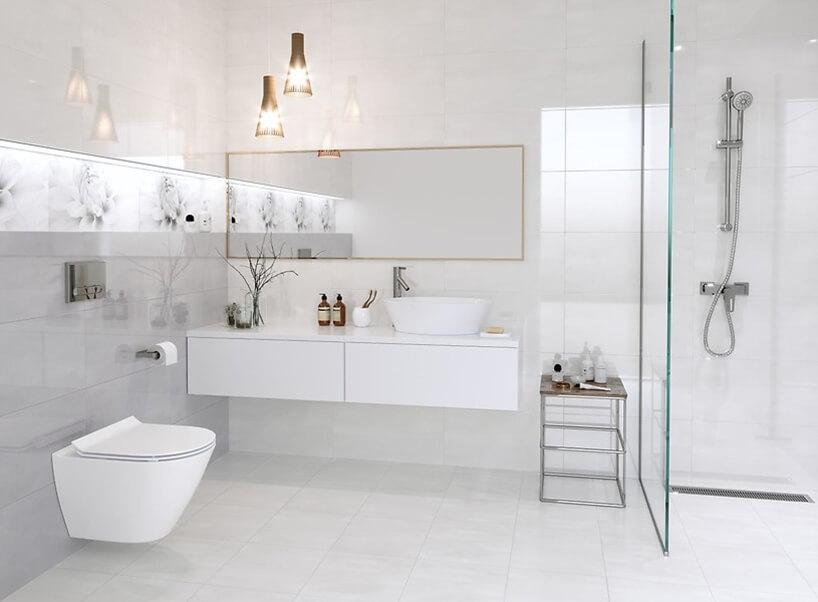 biała łazienka znatryskiem zduzym lustrem wcienkiej złotej ramce