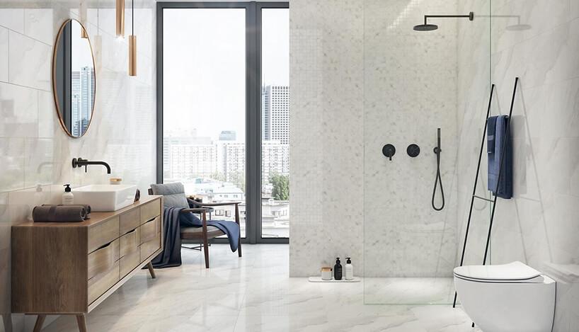 nowoczesna jasna łazienka zpłytkami Marble Charm od Opoczno zdrewnianą stojącą szafką na tle wysokiego okna wpłytkach