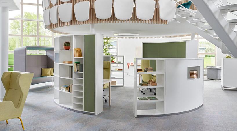 nowoczesna przestrzeń biurowa od Kinnarps białe owalne szafki zzielonymi elementami tworzące miejsce odpoczynku wewnątrz open space