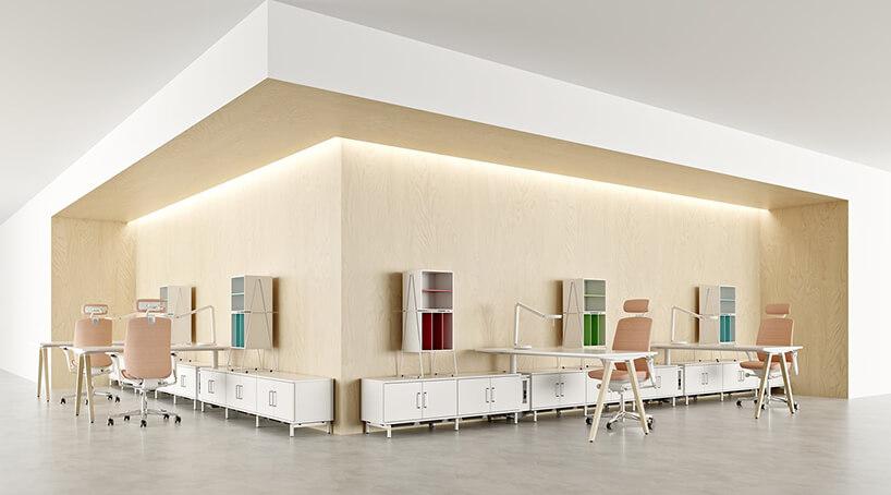 nowoczesna przestrzeń biurowa od Kinnarps biurka ułożone prostopadle do ściany na której zamontowane są różnokolorowe szafki