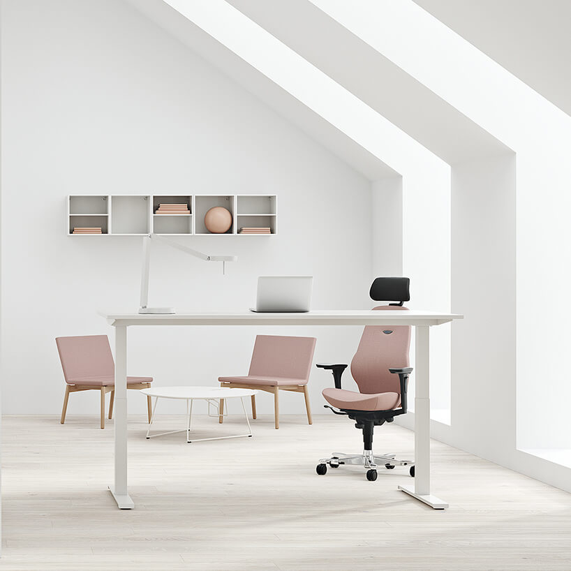 nowoczesna przestrzeń biurowa od Kinnarps jasne biuro zpochylonym sufitem zmeblami wróżowym kolorze ibiałe biurko zregulowaną wysokością
