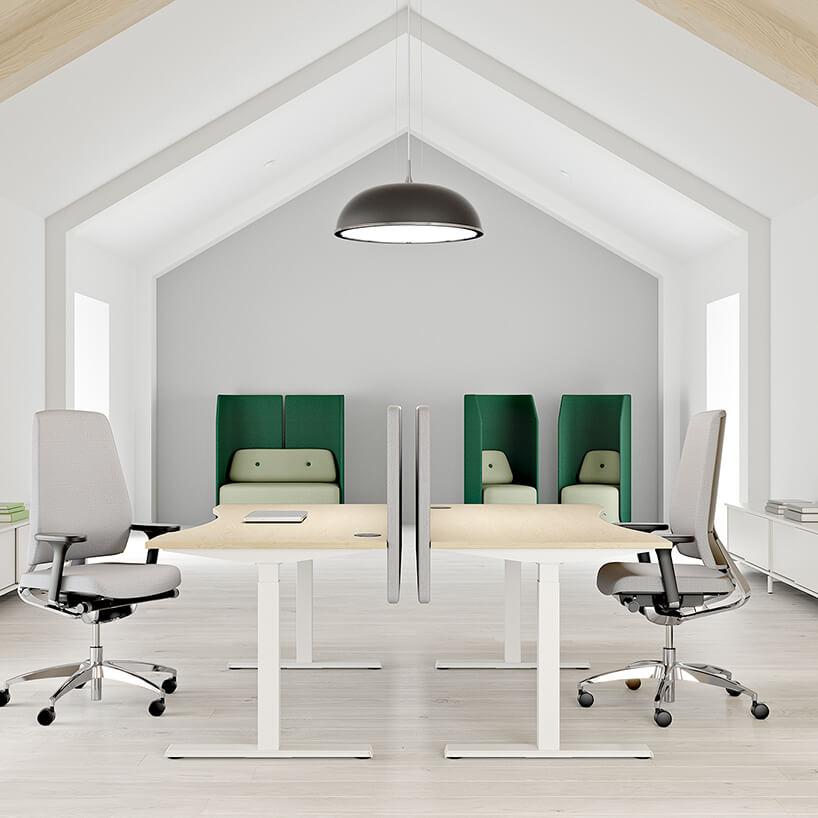 nowoczesna przestrzeń biurowa od Kinnarps dwa biurka ustawione na przeciw siebie zniską ścinką oddzielająca na tle zielonych boxów zwysokimi osłonami