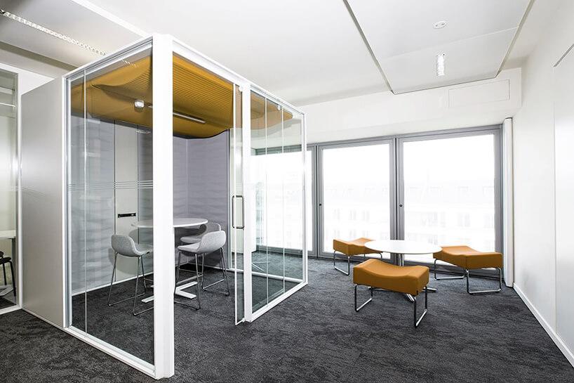nowoczesna przestrzeń biurowa od Kinnarps biały duży box do rozmów ztrzema krzesłami imałym stolikiem wbiałym open space