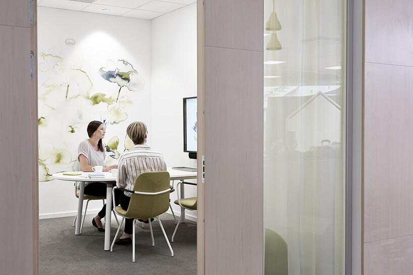 nowoczesna przestrzeń biurowa od Kinnarps dwie kobiety wbiałej sali konferencyjnej na tle grafiki na ścianie