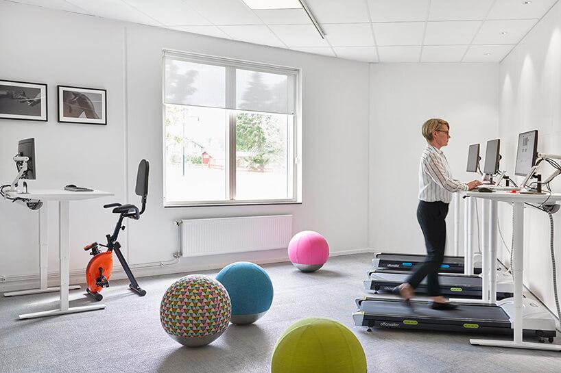 nowoczesna przestrzeń biurowa od Kinnarps kobieta podczas pracy przy biurku zamontowanym nad bieżnią do ćwiczeń