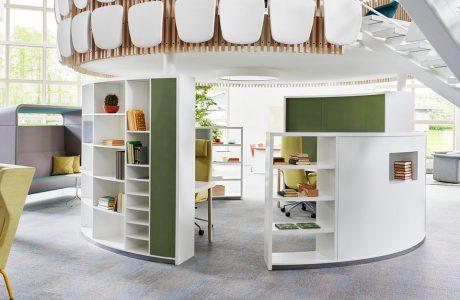 nowoczesna przestrzeń biurowa od Kinnarps białe owalne szafki z zielonymi elementami tworzące miejsce odpoczynku wewnątrz open space