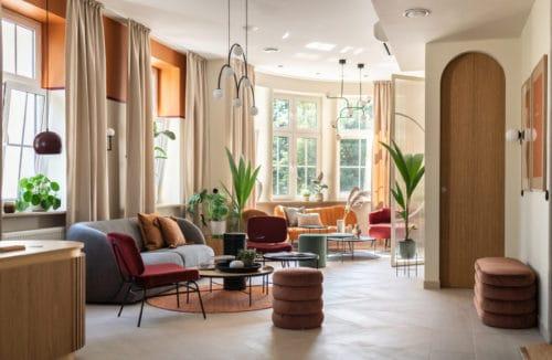 przestronne wnętrze z ciemnymi kanapami oraz okrągłymi stołami obok wysokich zielonych roślin