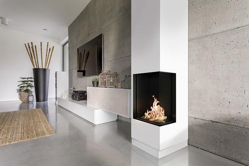 biały pionowy komin wformie prostokąta zczarną szybą zkominkiem obok betonowej ściany