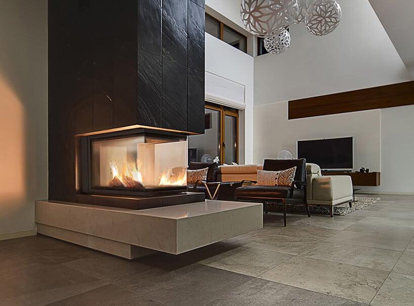 oszkolony kominek wzabudowie pionowej pokrytej ciemnymi kaflami zfakturą wdużym iwysokim salonie