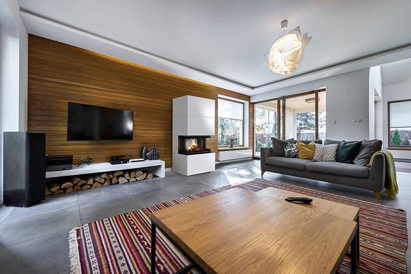 nowoczesny salon zkolorowym dywanem idrewnianym stołem