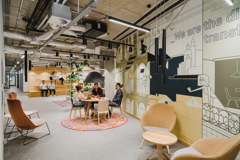 nowoczesne wnętrze open space intive troje pracowinków przy drewnianym stoliku