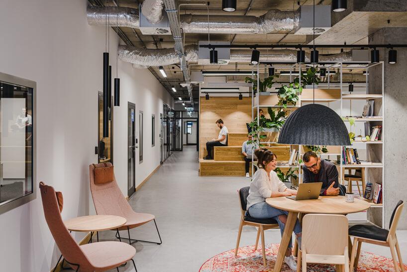 nowoczesne wnętrze open space intive różowe wysokie krzesła pod białą ścianą
