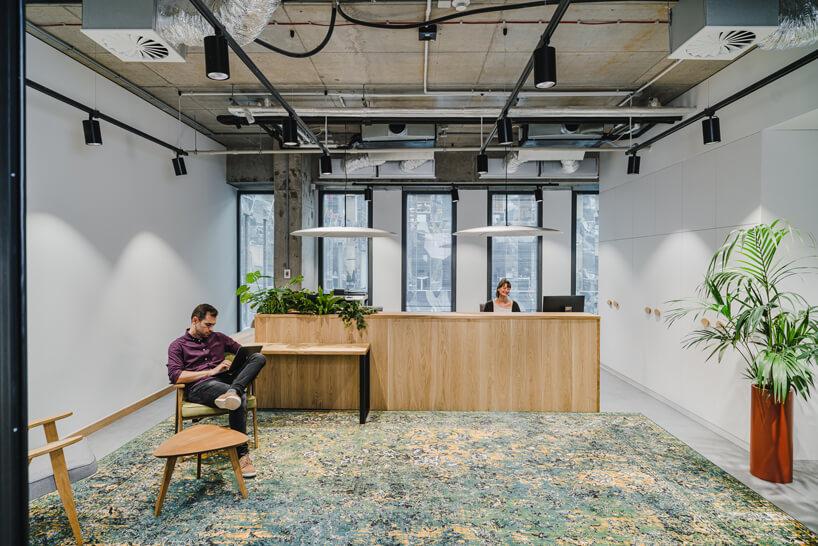 nowoczesne wnętrze open space intive drewniana resepcja obok białych szaf wścianie