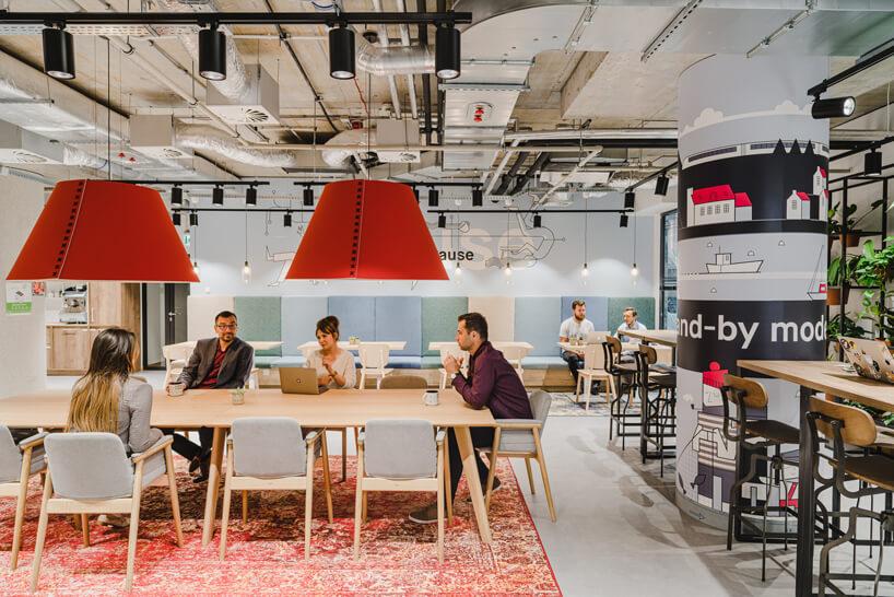 nowoczesne wnętrze open space intive przestrzeń zdużym drewnianym stołem pod dużymi czerwonymi lampami