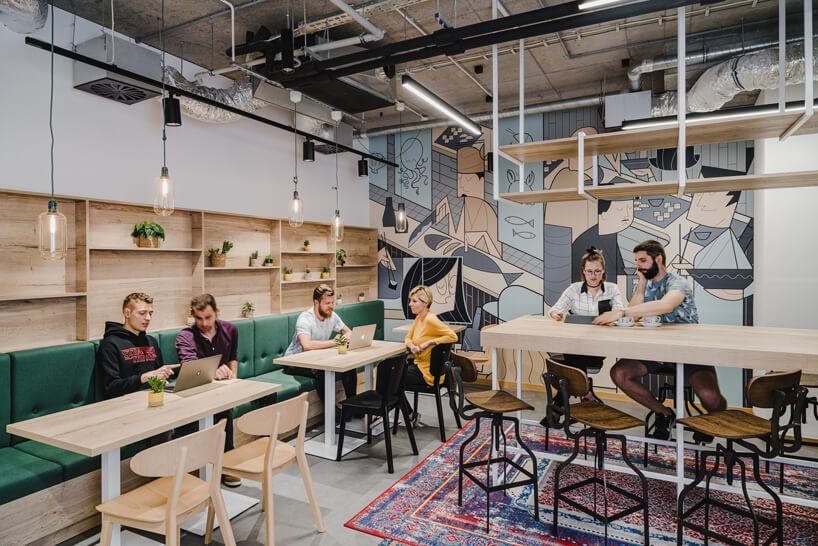 nowoczesne wnętrze open space intive wysoki drewniany stół obok małych stolików wzdłuż zielonej ławki