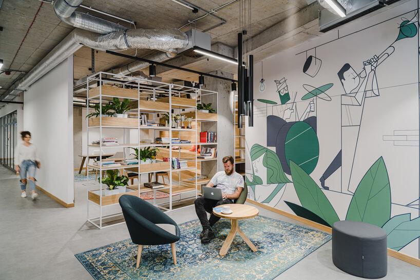 nowoczesne wnętrze open space intive mały drewniany stolika zdwoma ciemnymi fotelami na tle szafki obok ściany znamalowanym zespołem muzycznym