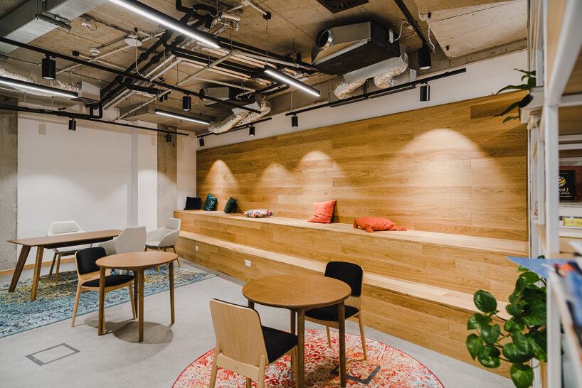 nowoczesne wnętrze open space intive małe stolik zkrzesłami na tle dwupoziomowej drewnianych schodów do siedzienia