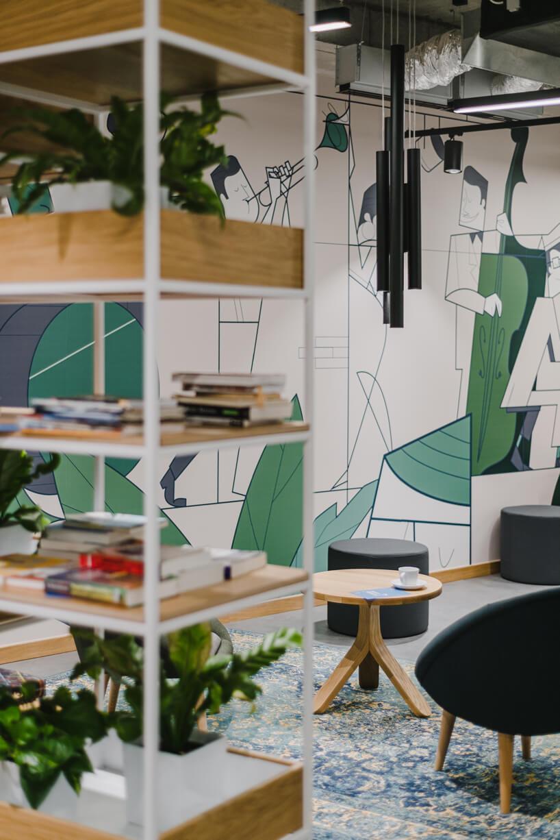 nowoczesne wnętrze open space intive detal białej szafki zdrewnianymi półkami na tle małego drewnianego stolika zciemnym fotelem