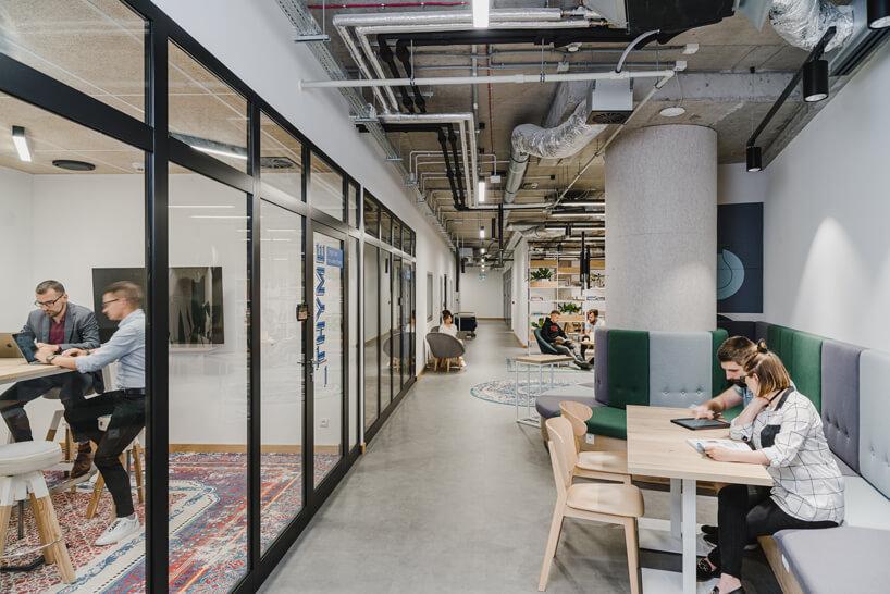 nowoczesne wnętrze open space intive oddzielona przestrzeń konferencyjna obok długiej ławki przy ścianie zdrewnianym stolikiem
