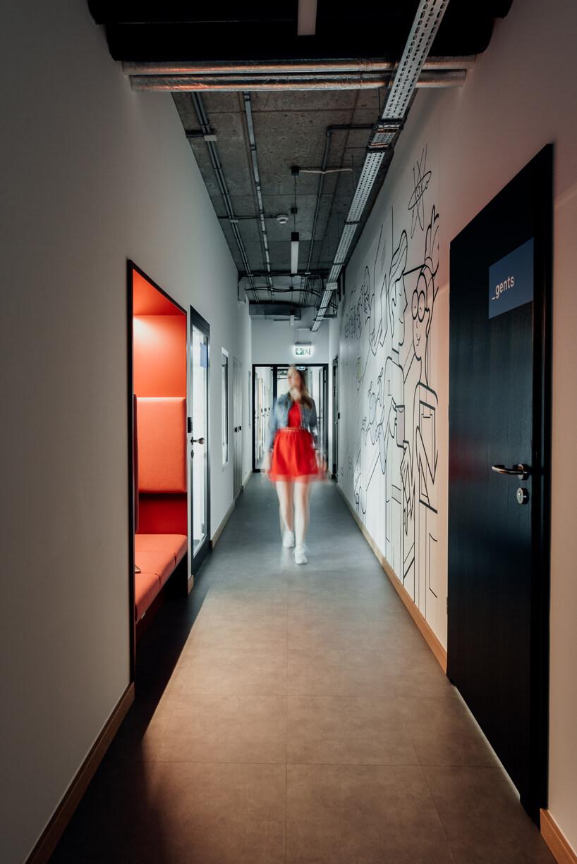 nowoczesne wnętrze open space intive długi biały hol zróznymi drzwiami iczerwoną wnęką zsiedziskiem