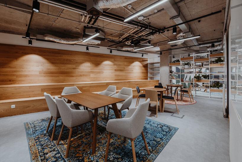 nowoczesne wnętrze open space intive trzy stoliki oróznych wielkościach zkrzesłami na tle drewnianej ściany zdwu stopniowym siedziskiem