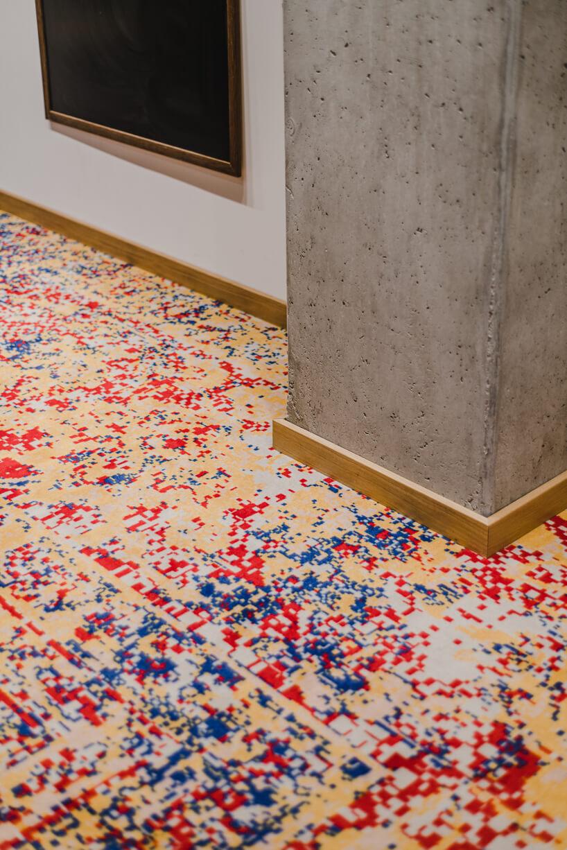 nowoczesne wnętrze open space intive kolorowa wykładzina wkanciaste wzory przy drewnianej liście ibetonowym filarze