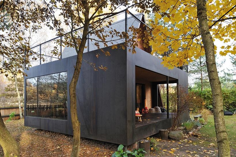 szara kostka zdużymi oknami ibalustradą na dachu przy drzewie na podwórku