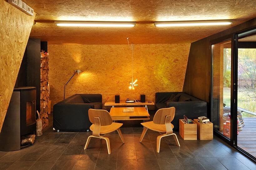 ściany pokryte płytą osb wpomieszczeniu ze skórzanymi sofami iczarnym kominkiem