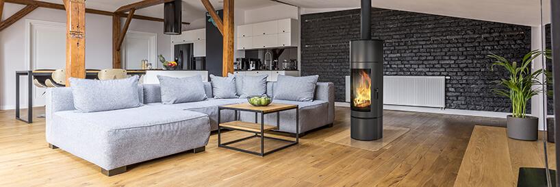czarny okrągły kominek marki Kratki wcentrum dużego salonu zdrewnianą podłoga iszarą sofą