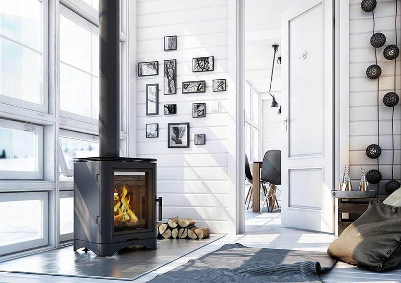 czarny elegancki kwadratowy wolnostojący kominek wbiałym salonie na tle ściany zoknami