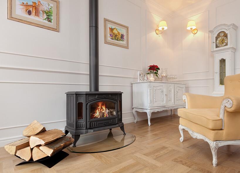 czarny elegancki niski wolnostojący kominek marki Kratki na nóżkach weleganckim białym salonie zklasycznymi meblami