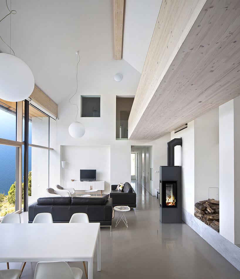 biały wysoki salon ze skośnym sufitem iczarnym wysokim kominkiem wolnostojącym marki Kratki