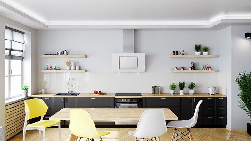 połączona zjadalnią biała kuchnia zczarnymi szafkami