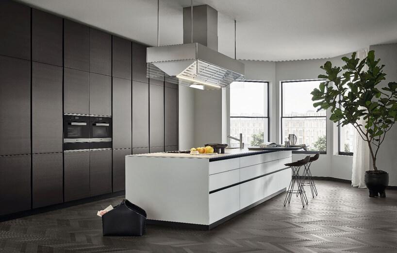 biała szafka kuchenna idwa czarne krzesła na tle szarej kuchni