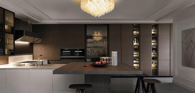 brązowy stół biało brązowa szafka kuchenna ze zlewozmywakiem kryształowa lampa na tle brązowych szafek
