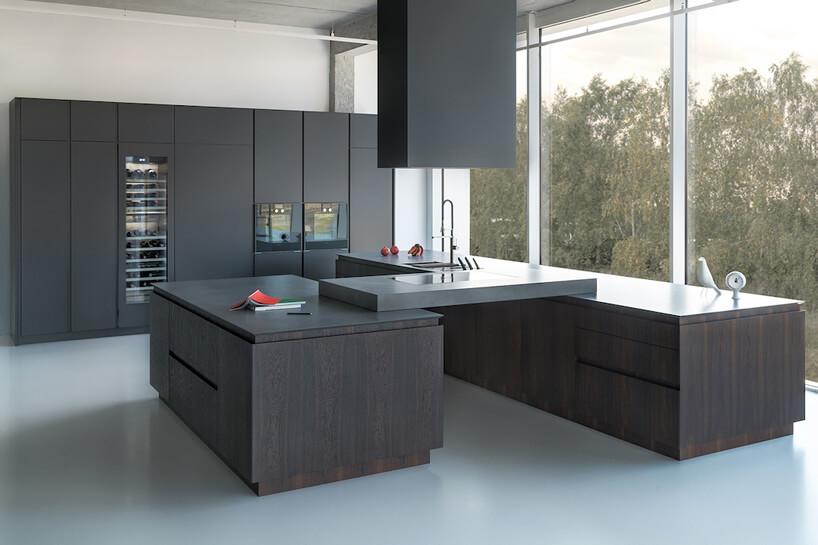 ciemno brązowe szafki kuchenne połączone piecem indukcyjnym na tle czarnych szafek