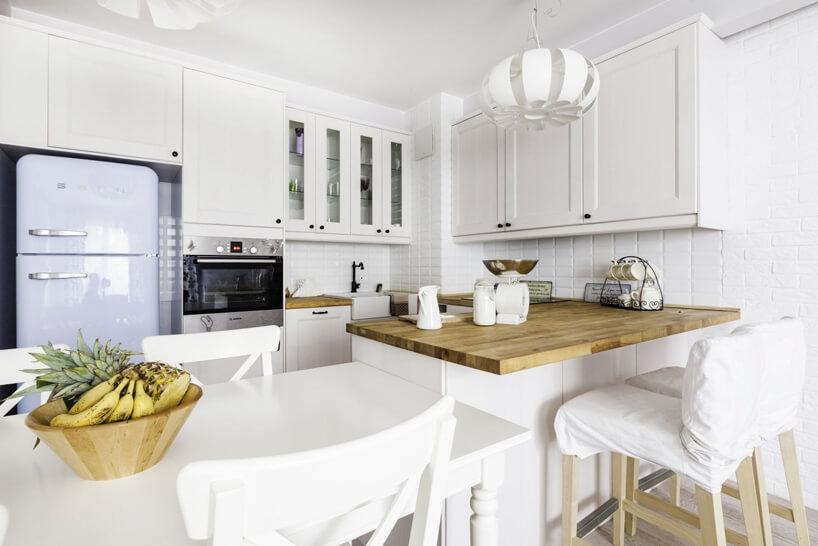 biały stół ikrzesła brązowy blat kuchenny białe szafki wiszące wkuchni