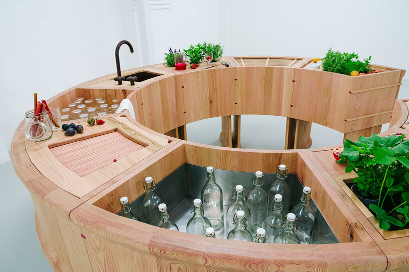 drewniany bar szkalne butelki zlewozmywak roślinki na tle białej ściany