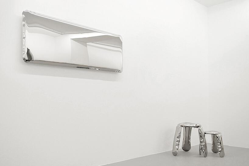 prostokątne lustro Tafla IQ od Oskara Zięty nad dwoma wyjątkowymi stołkami