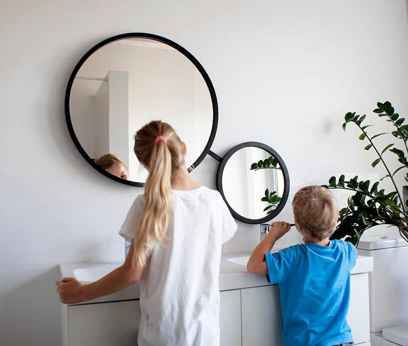 dwa połączone lustra okrągłe Scandi-Duo od GieraDesign oróżnej wielkości wczarnej ramce wjasnej łazience