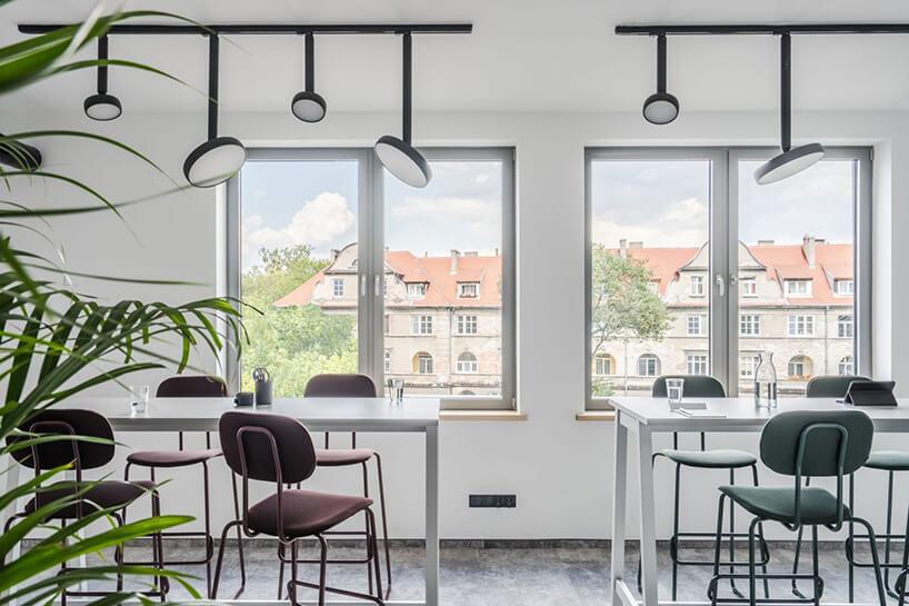 jasna przestrzeń biurowa zwysokimi białymi biurkami zbordowymi krzesłami New School od MDD