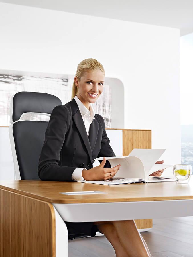 kobieta wgarniturze przy drewnianym biurku