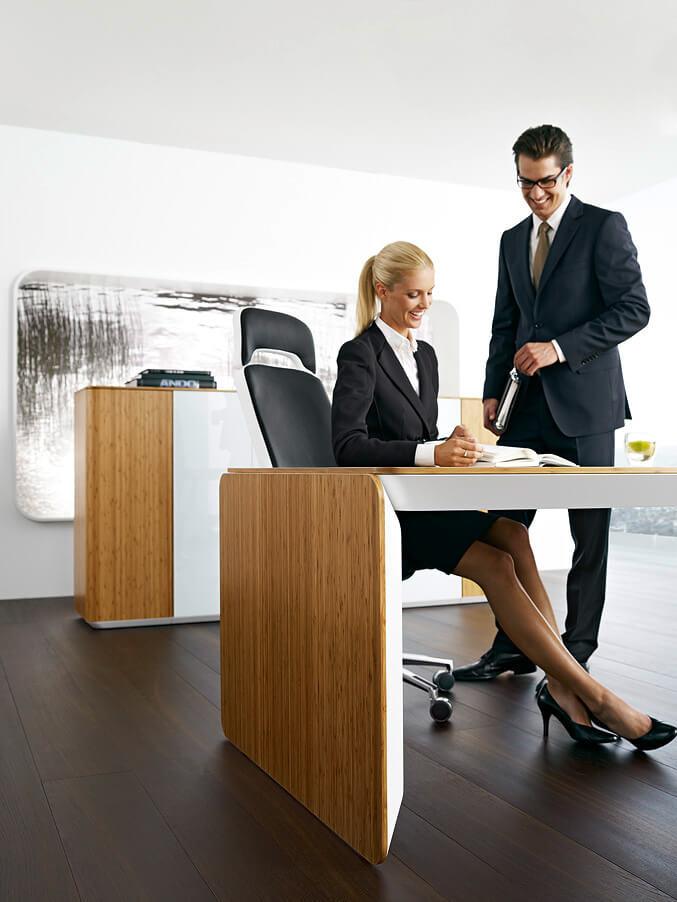 pracownicy korzystjący znowoczesnego biurka