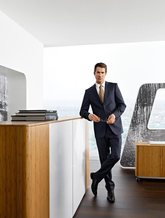 człowiek wgarniturze obok stylowej komody