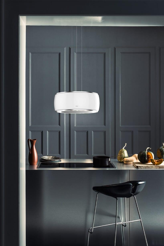 nowoczesny biały okap kuchenny Soffio zkolekcji Circle.Tech od Falmec nad ciemno szarą wyspą kuchenną