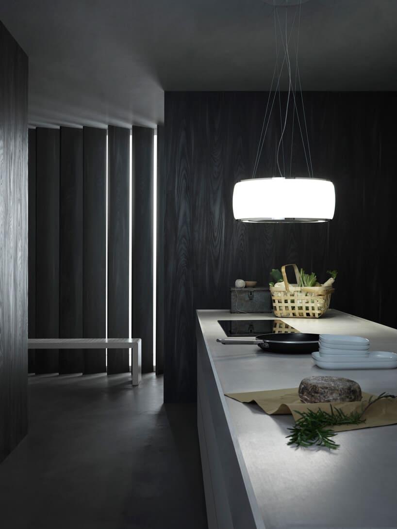 elegancki okap kuchenny Soffio zkolekcji Circle.Tech od Falmec nad długą jasną wyspą kuchenną na tle ciemnej ściany