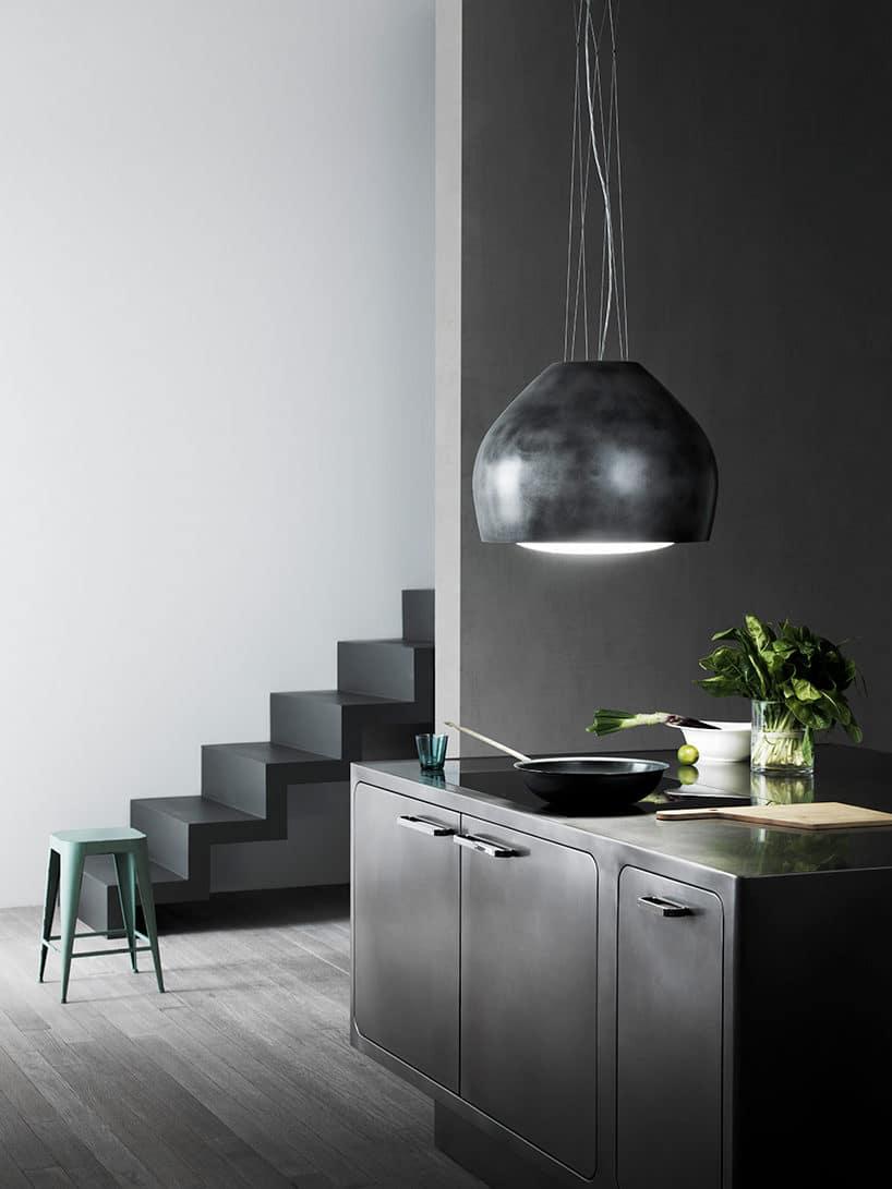 elegancki podwieszany pod sufitem kap kuchenny Sophie od Falmec nad matową czarną wyspą kuchenna