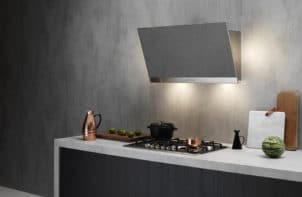 elegancki ścienny okap kuchenny Trim od Falmec w szarym aneksie kuchennym z biało czarną zabudową