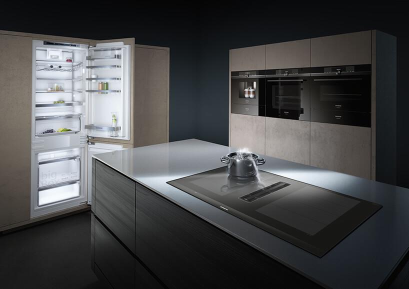 elegancka nowoczesna płyta grzewcza EX875LX67E od Siemens wszklanym blacie dużej wyspy kuchennej zdodatkową funkcją wyciągu