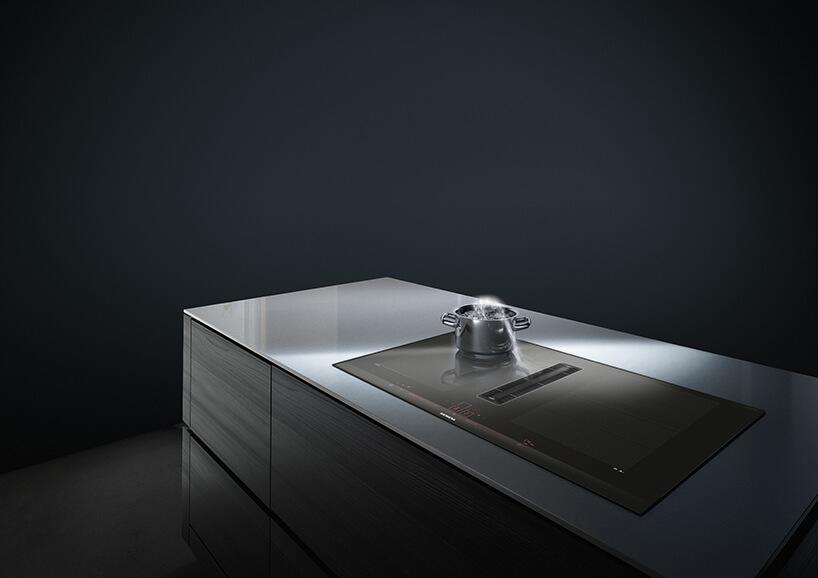 elegancka nowoczesna płyta grzewcza EX875LX67E od Siemens wszklanym blacie dużej wyspy kuchennej postawionym garnkiem zgotująca się wodą